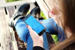 Joven con smartphone Facebook Rooms